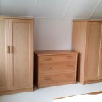 A pair of small oak wardrobes and a chest of drawers designed to fit under a low sloping ceiling.