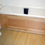 Hinged bath panel in Canadian Maple providing storage beneath the bath.