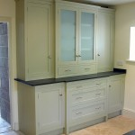 A large built-in dresser with a painted finish and slate worktop