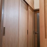 Oak sliding door wardrobes built into a narrow corridor.