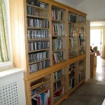 A built-in bookcase in a passageway. The timber is Canadian Maple with a linseed oil finish. All the units have toughened glass doors