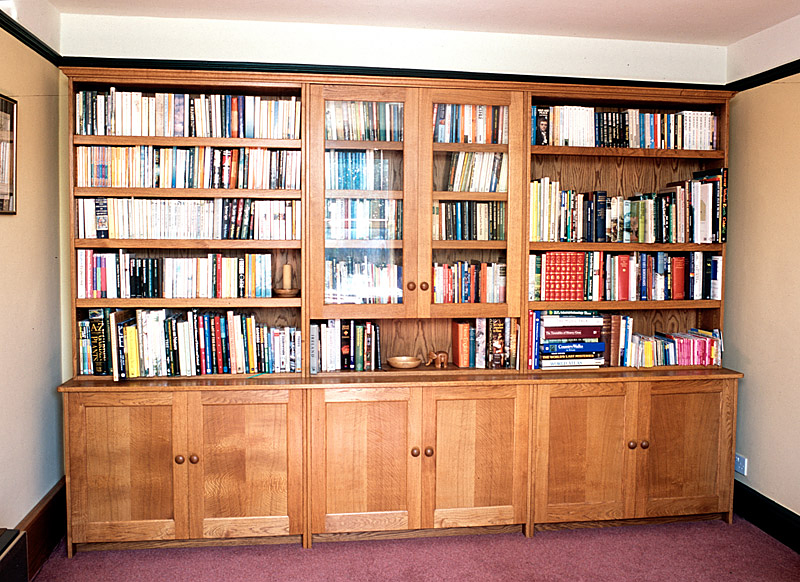 Oak bookcase with glazed doors. All the shelves are fitted on adjustable bookcase track. The Oak is finished with a light stain and Danish oil