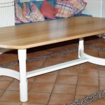 Refectory style table which has a Maple top with a lacquered finish and a base with turned legs and laminated curved rails, which are painted