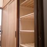 Oak sliding door wardrobes built into a narrow corridor.